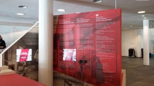 Ausstellungsstation im Foyer des DSM. Bildschirme mit Dokumentarfilmen, in der Mitte Hörmuscheln, dreisprachige Textwand.